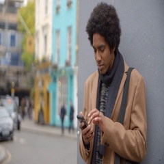 Young Man Using Phone On Busy City Street Stock Footage