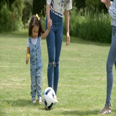 Mum and friends kicking a ball outdoors with young daughter Stock Footage
