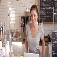 Woman behind the counter of a coffee shop crosses arms Stock Footage