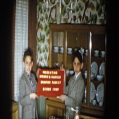 1959: two little lads in similar dressing holding a board in red and white Stock Footage