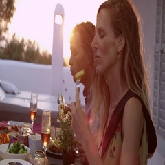 Handheld close up of two couples eating dinner on a terrace, shot on R3D Stock Footage