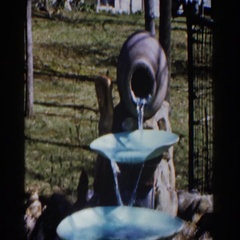 1959: water flows through garden fountain from urn onto two lower trays MICHIGAN Stock Footage