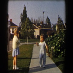 1958: a cute little boy in overalls running down the sidewalk from his family Stock Footage