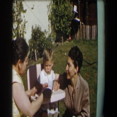 1958: two middle-aged women are helping a little boy eat cake  Stock Footage