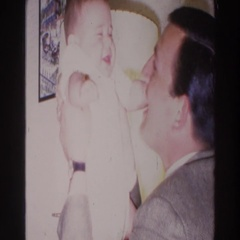 1966: man makes baby laugh by kissing its belly; men drink while watching child Stock Footage