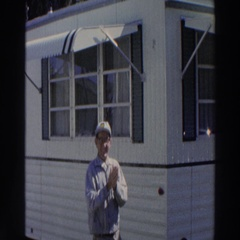 1966: trailer home by a beach with a man standing rubbing his hands PUERTO RICO Arkistovideo