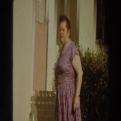 1966: a woman wearing a purple dress walking outside a building PUERTO RICO Stock Footage