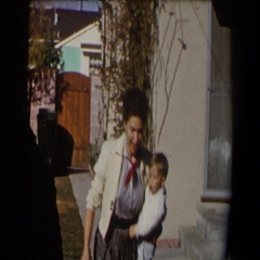 1958: mother with her child outside hanging laundry on clothing line and excited Stock Footage
