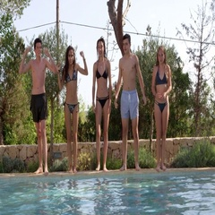 Five teenagers jumping into an outdoor pool together, shot on R3D Stock Footage