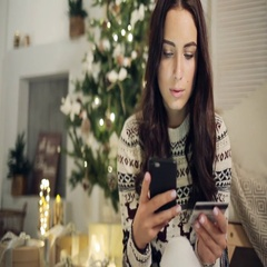 Young woman buying gifts with credit card on Christmas at home Stock Footage