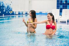 Two young beautiful brunette girls in swimming pool indoors Stock Photos
