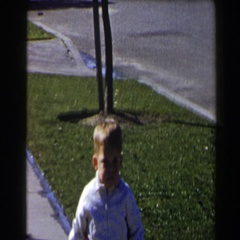 1958: young boy slowly walking down the sidewalk in a deserted neighborhood Stock Footage