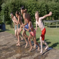 Group Of Children Jumping Into Outdoor Swimming Pool Stock Footage