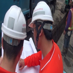 Two asian operators or workers are looking at blueprints on a highway. Stock Footage