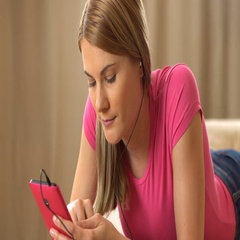 Beautiful attractive young woman in a pink t-shirt with a pink smartphone lying Stock Footage