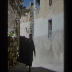 1960: a woman wearing a long coat walking in the alley ISRAEL Stock Footage