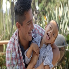 Father Tickling Son As They Sit In Garden Together Stock Footage