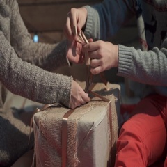 Hands of young couple wapring a xmas present Stock Footage