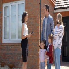 Realtor Outside House For Sale With Young Family Stock Footage