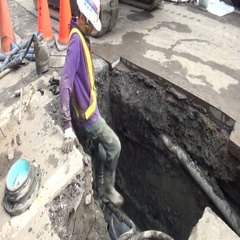 A worker is tucked into a ditch to fit a new water pipe. A broken water pipe. Stock Footage