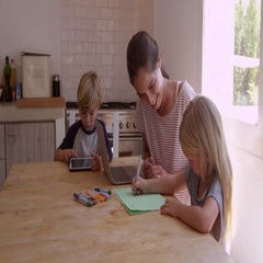 Mum and two kids working at the kitchen table, shot on R3D Stock Footage