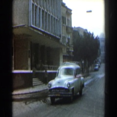 1960: a motor vehicle driving on the street past a building ISRAEL Stock Footage