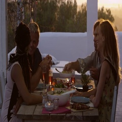 Two couples eating dinner at a table on a rooftop terrace, shot on R3D Stock Footage