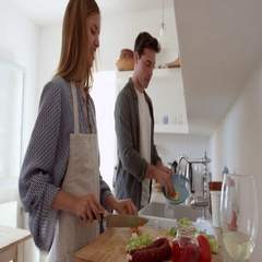 Young adult couple talking as they prepare food and wash up, shot on R3D Stock Footage