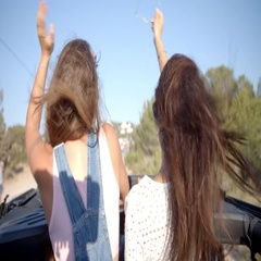 Two female friends standing up in the back of a moving car Stock Footage