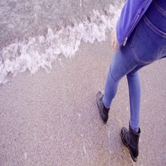 Blonde woman with long hair walks back from water on the beach Stock Footage