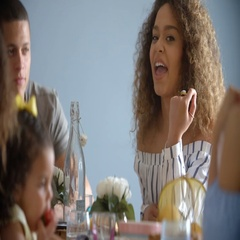 Adult couple and young girl sit talking around a table Stock Footage