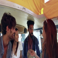 Four friends on a road trip talk in the back of a camper van Stock Footage