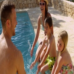 Family On Vacation Relaxing By Outdoor Pool Stock Footage