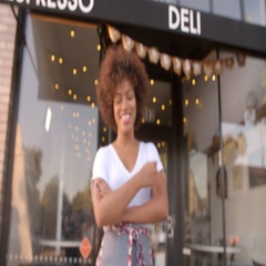 Black female owner walks into focal plane in front of cafe Stock Footage