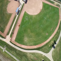Aerial view of a grassy area for sports entertainment near a body of water Stock Footage