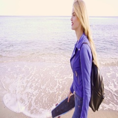 Blonde woman with long hair walks by the sea with skate Stock Footage