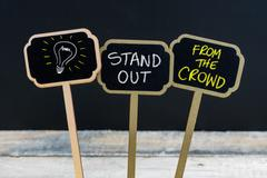 Concept message STAND OUT FROM THE CROWD and light bulb as symbol for idea  Stock Photos