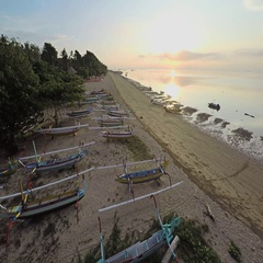Aerial shot of sunrise in Sanur with a lot of traditional boat on the beach Stock Footage