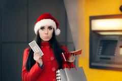 Christmas Woman Holding One Dollar in Front of an ATM Stock Photos