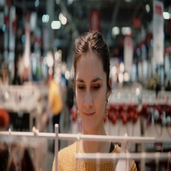Attractive happy young woman chooses at store some goods. decor for home Stock Footage