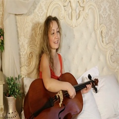 Young woman with long hair sitting on a bed with a musical instrument. Stock Footage
