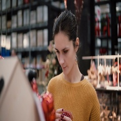 Young attractive brunette girl at the store chooses bright red Christmas decor Stock Footage