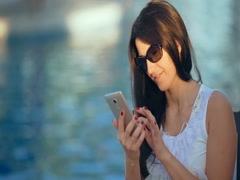 Happy young woman using a smart phone near the swimming pool Stock Footage