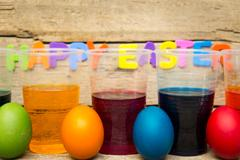 Colorful easter eggs and cups of dye in front of a wooden background Stock Photos