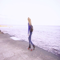 Young beautiful girl rides her skate board near the sea Stock Footage
