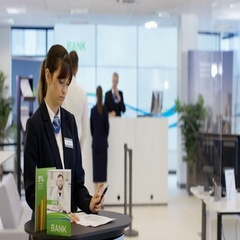 4K Bank worker on information desk giving help & advice to customers Arkistovideo