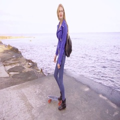 Young beautiful girl stands with her skate board near the sea Stock Footage