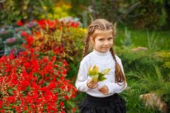Sweet girl and fallen leaves Stock Photos