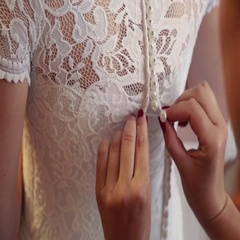 Getting ready for wedding ceremony. Mother or bridesmaid helping young bride to Stock Footage
