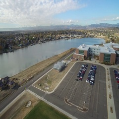 Aerial view of a city around a lake with many buildings, courts, vehicles, etc. Stock Footage